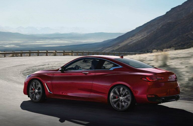 Exterior view of the rear of a red 2019 INFINITI Q60 driving down a winding mountain road