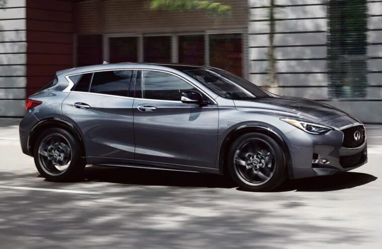 Exterior view of a grey 2019 INFINITI QX30 driving down a city street