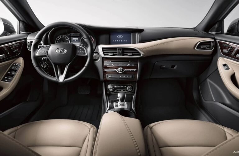 Interior view of the front seating area, steering wheel, and dashboard inside a 2019 INFINITI QX30