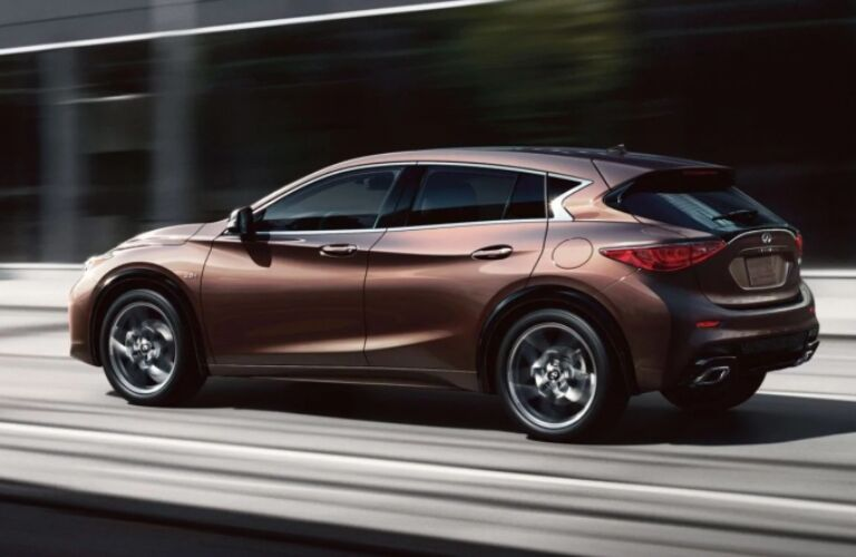 Exterior view of the rear of a bronze 2019 INFINITI QX30 driving down a city street