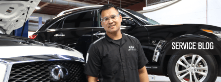 man smiling in service center by two infiniti vehicles