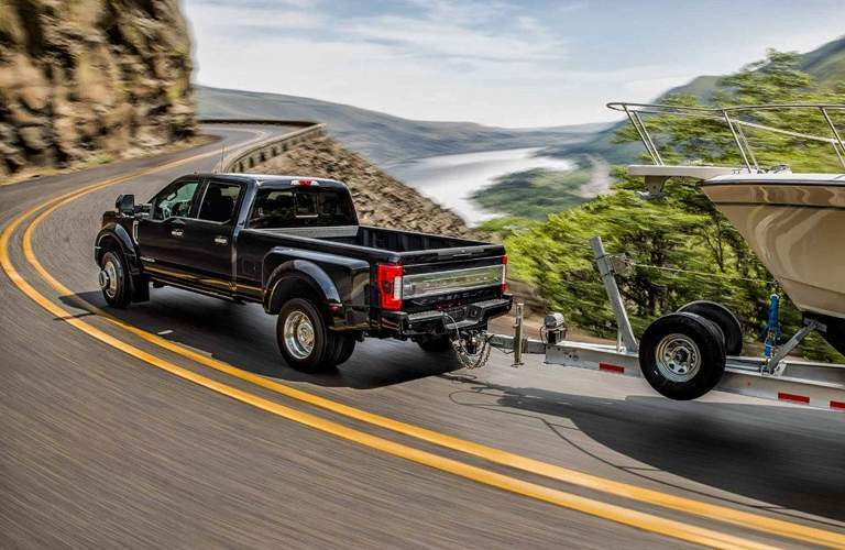 2018 Ford Super Duty F-250 driving on a highway around a curb towing a giant boat