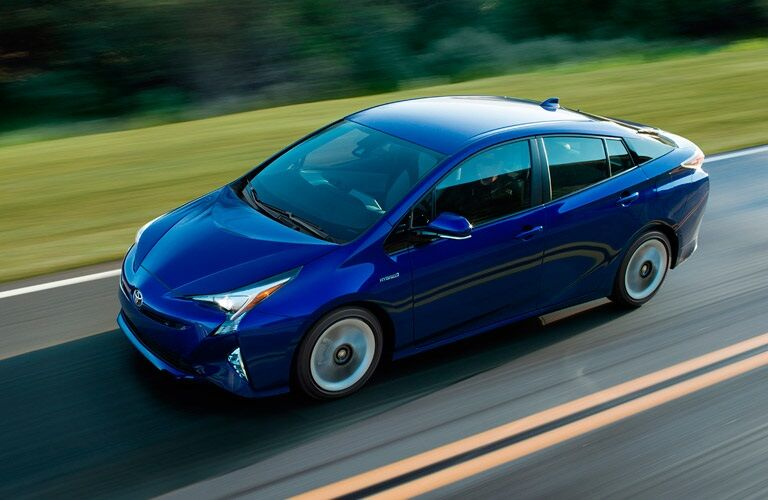blue 2017 Toyota Prius driving on road