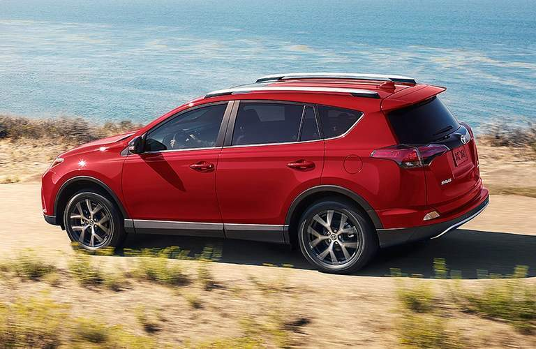 red 2017 Toyota RAV4 driving on gravel road near water