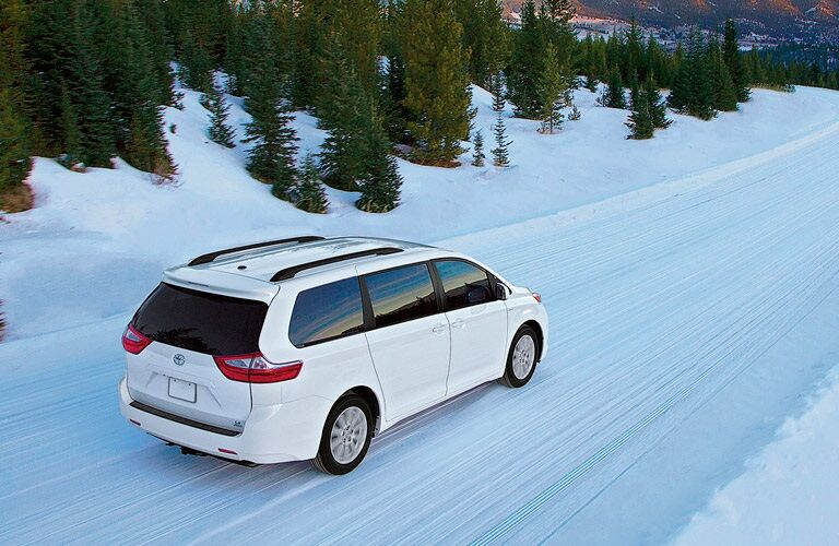 White 2017 Toyota Sienna driving in snow with all-wheel drive