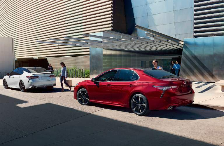 Two, 2018 Toyota Camry's parked in front of a modern building