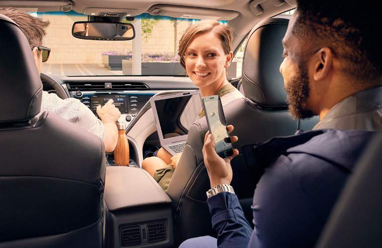 group of friends using technology in 2018 Toyota Camry