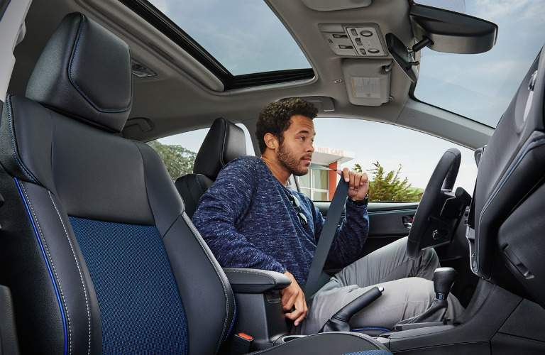 man buckling his seat belt in the 2018 Toyota Corolla