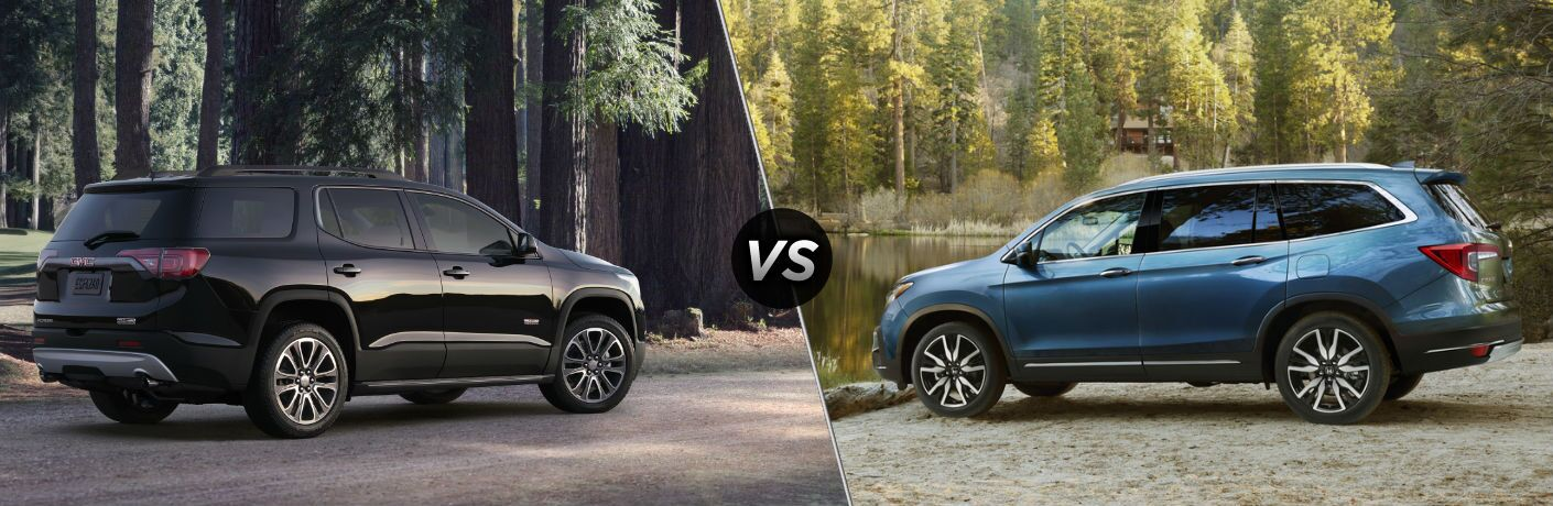 "Passenger side exterior view of a black 2019 GMC Acadia on the left ""vs"" a driver side exterior view of a blue 2019 Honda Pilot on the right"