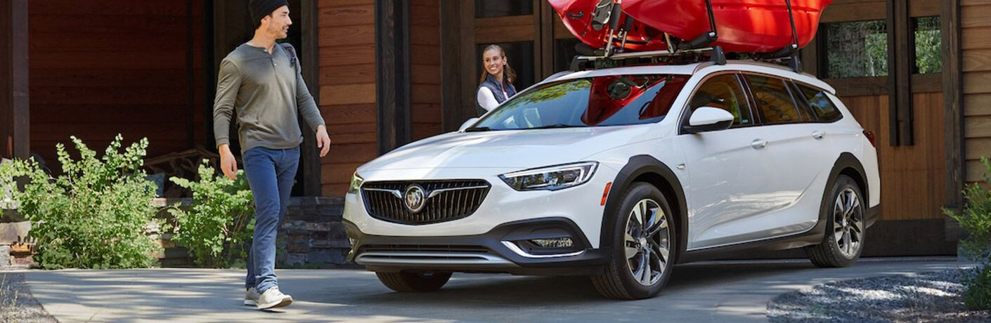 Happy couple loading a kayak onto the roof rack of a white 2018 Buick Regal TourX
