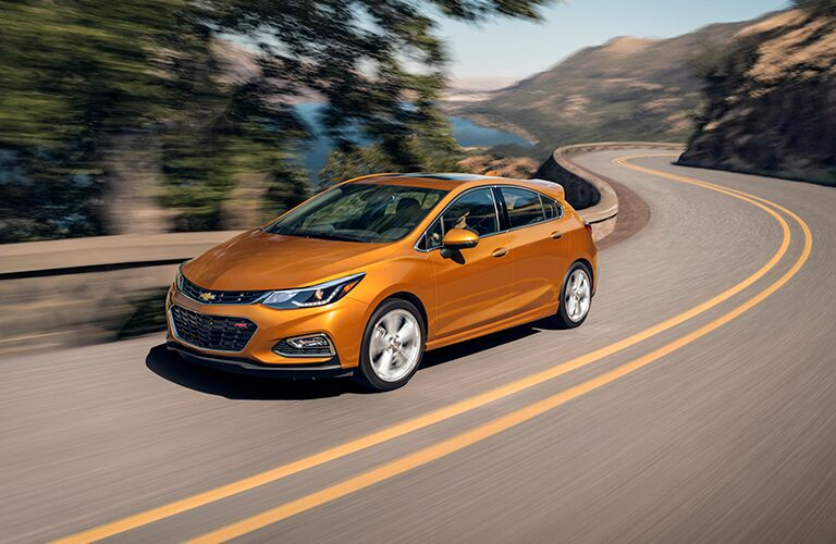 Driver side exterior view of a an orange 2018 Chevy Cruze Hatchback