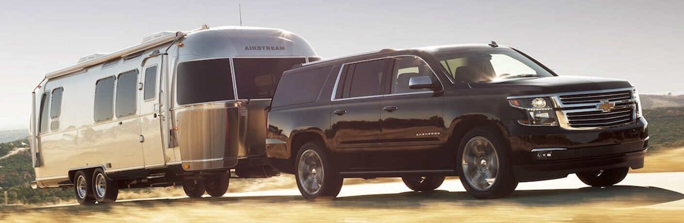 Passenger side exterior view of a black 2018 Chevy Suburban towing an Airstream trailer
