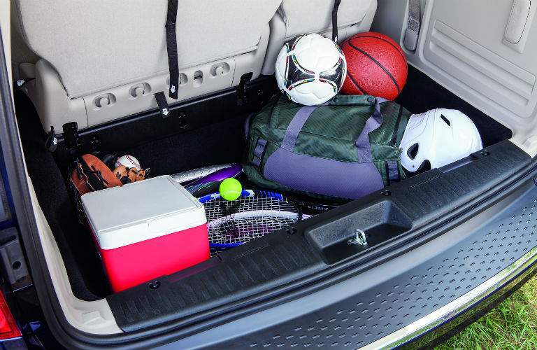 Rear cargo area of the 2018 Dodge Caravan filled with sports equipment
