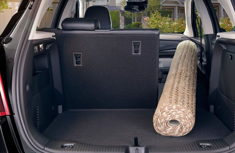 Rear seat split-folded and the front passenger seat folded down in the 2019 Buick Encore to accommodate a long rug