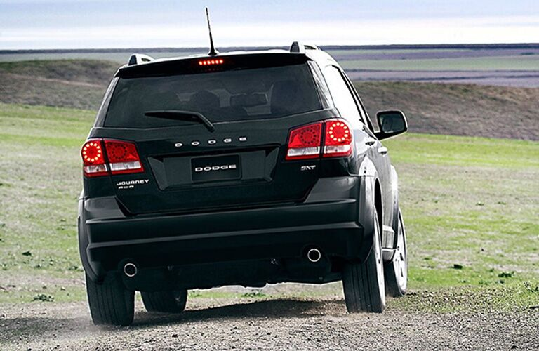 2019 Dodge Journey exterior rear view as it drives in a gravelly field