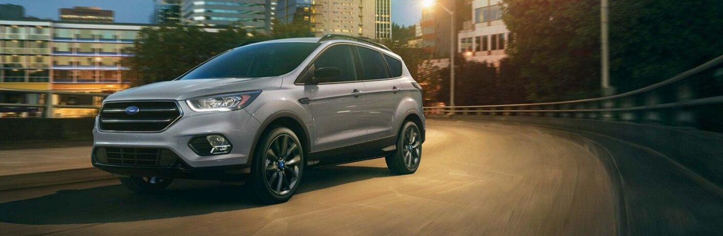 Exterior view of a grey 2019 Ford Escape driving down a city street