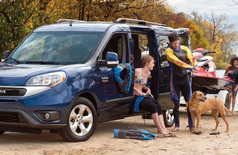 Young couple removing wet suits next to a Blue 2019 Ram ProMaster City Wagon
