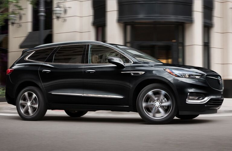 Black 2020 Buick Enclave driving by a white building