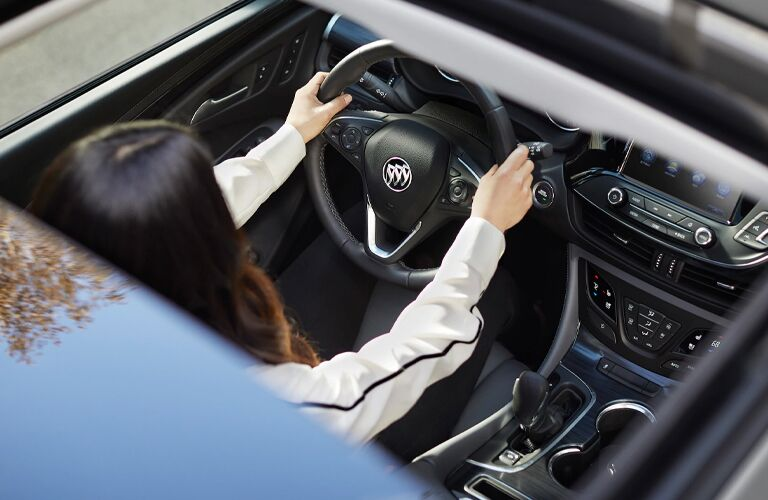View of a female driver through the moonroof of a 2020 Buick Envision