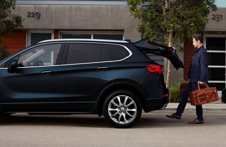 A man using the Hands-Free Power Liftgate on a dark blue 2020 Buick Envision