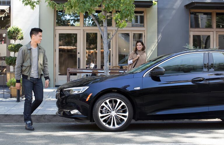 Man and woman approaching parked 2020 Buick Regal Sportback