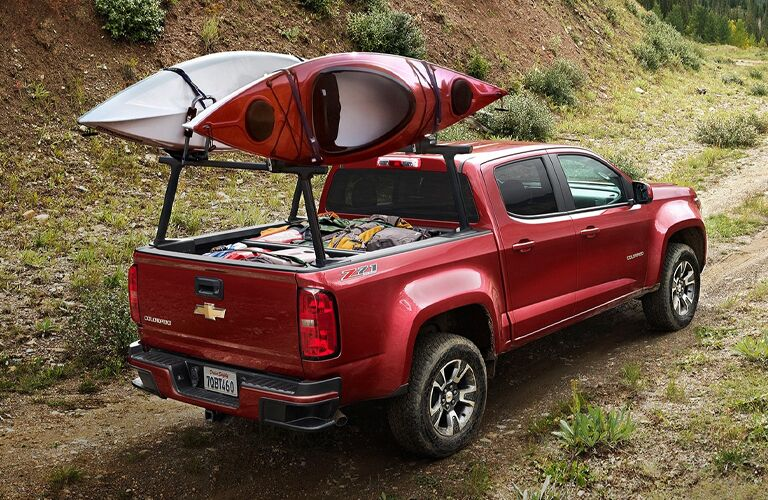 Red 2020 Chevrolet Colorado with kayaks on a rack above the pickup bed