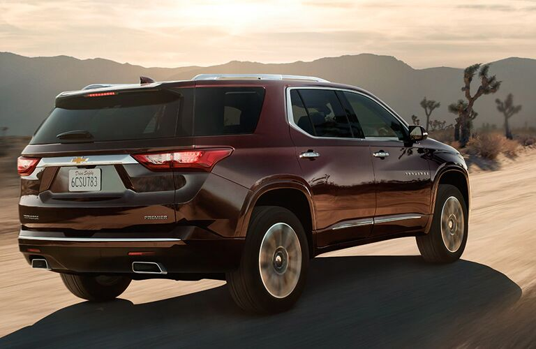 Reddish brown 2020 Chevrolet Traverse driving by some Joshua trees