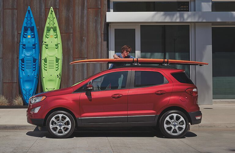 A man placing a surfboard on the roof of a red 2020 Ford EcoSport