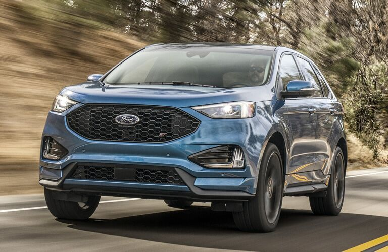blue 2020 Ford Edge driving on hilly wooded highway