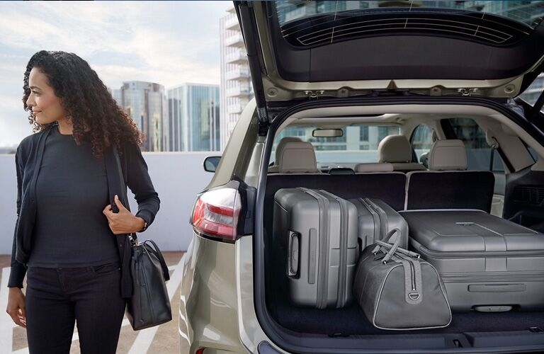 woman loading luggage into cargo area of 2020 Ford Edge