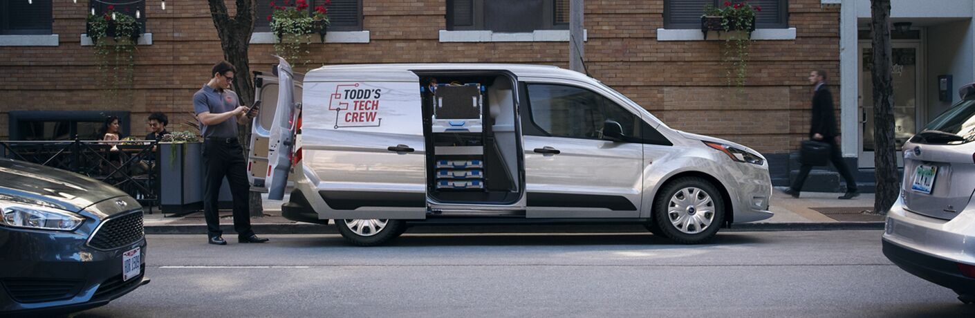 Silver 2020 Ford Transit Connect Cargo Van parked near a brick building