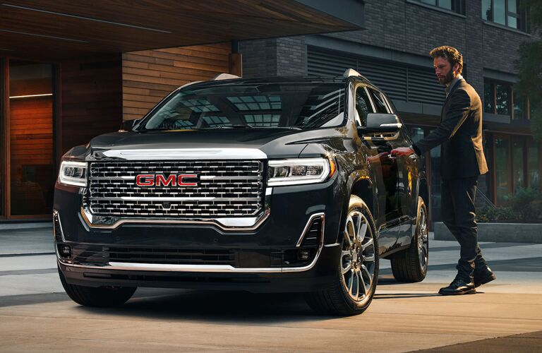 A man opening the door of a black 2020 GMC Acadia
