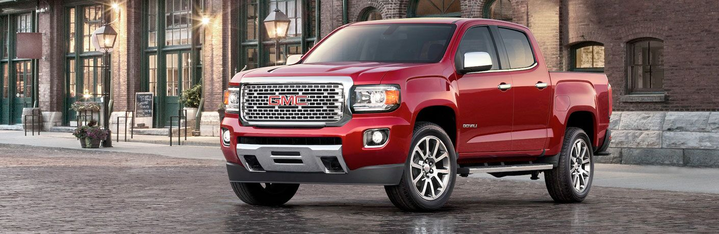Red 2020 GMC Canyon parked in front of a brick building