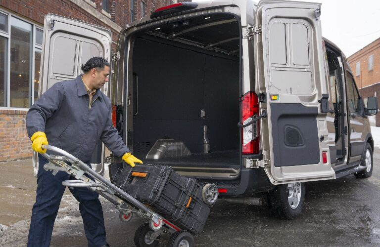 A man loading items into a white 2020 Ford Transit Cargo Van