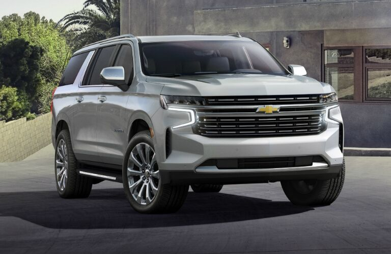 Silver 2021 Chevrolet Suburban parked near a modernistic house
