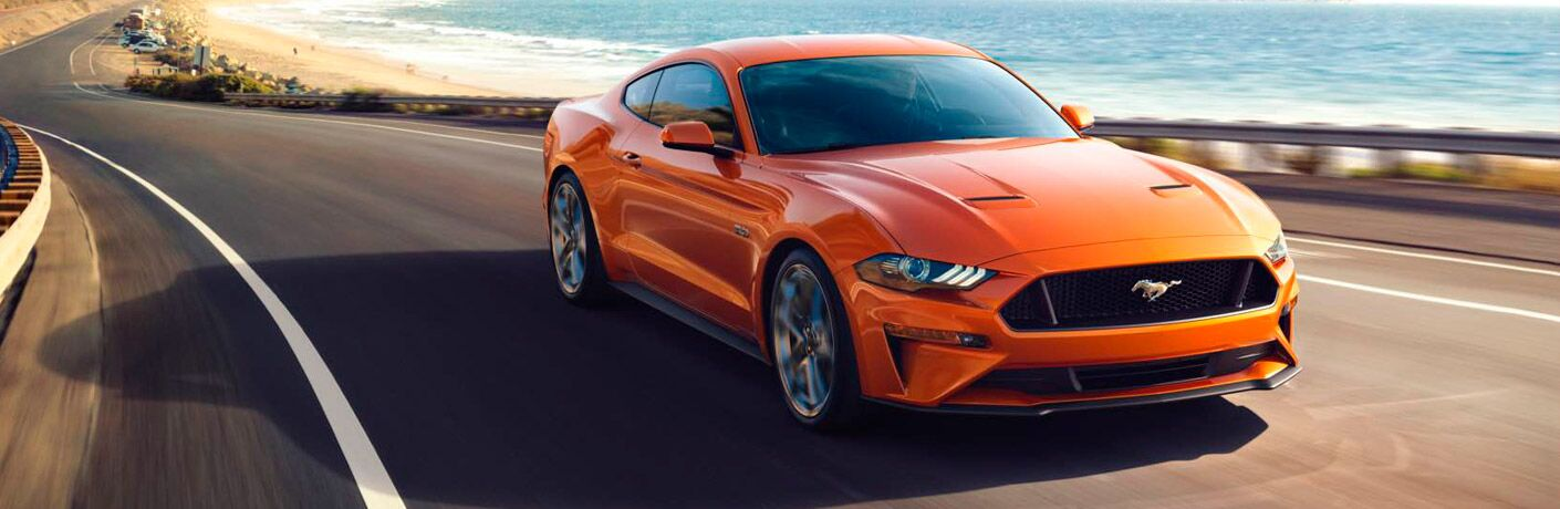 Orange Ford Mustange cruising down a seaside highway