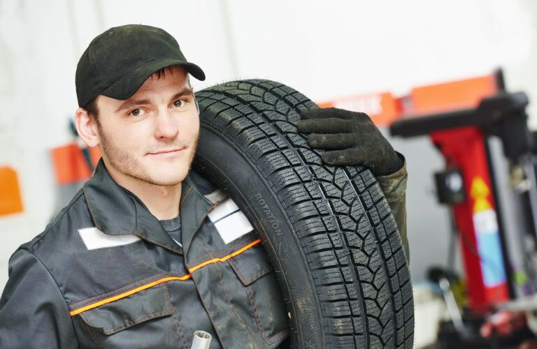 Mechanic with a tire over his shoulder