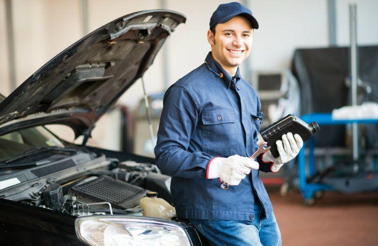 Mechanic with bottle of automotive oil near an open hood