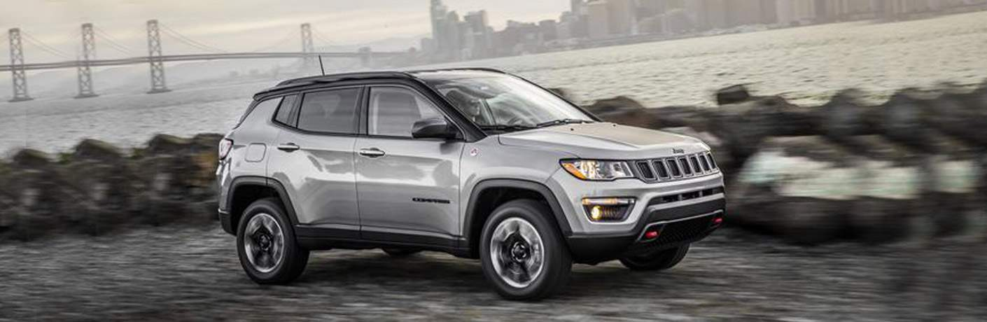 silver 2018 jeep compass driving with bridge and city skyline behind it