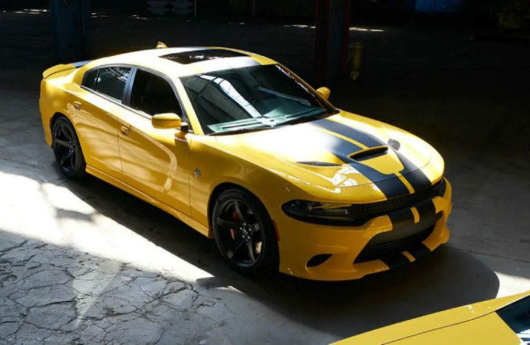 2018 Dodge Charger S/T Scat Pack in yellow with black stripes parked in an empty warehouse