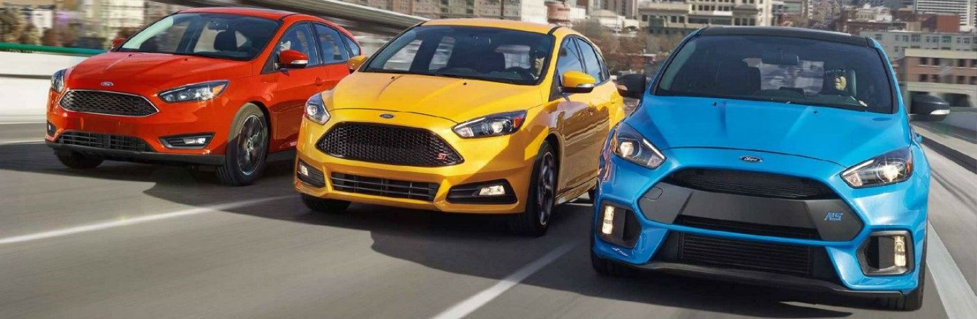 2018 Ford Focus ST, SEL and RS driving next to each other on a road