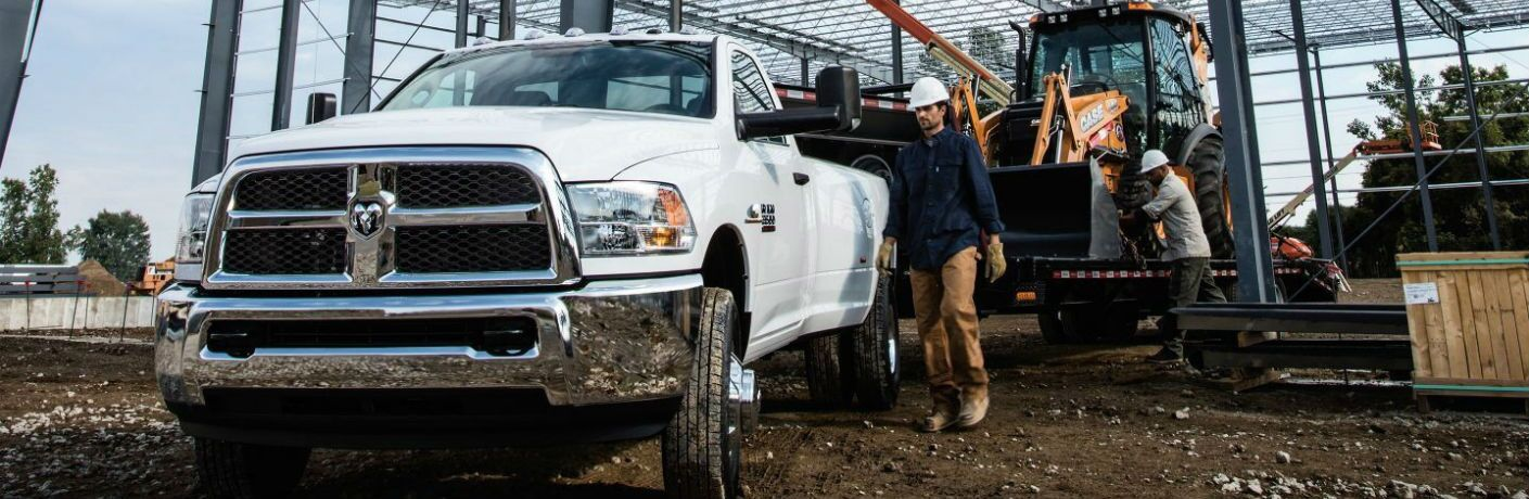 2018 Ram 3500 at a construction site towing a backhoe