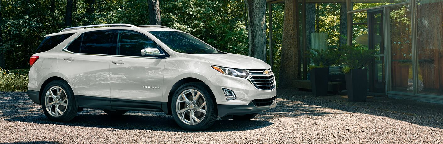 2019 Chevy Equinox exterior side shot with white paint color parked on a gravel plot within a summer forest