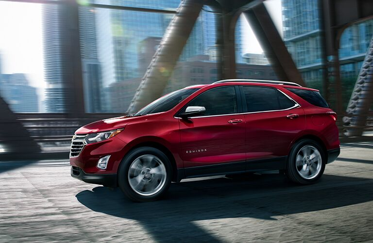 2019 Chevy Equinox exterior side shot with red paint color parked under a construction site of metal girders