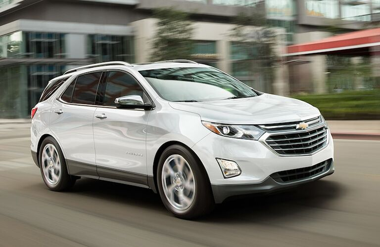 2019 Chevy Equinox exterior shot with white paint color driving through a city as the background blurs through speed