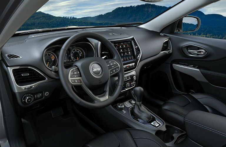 2019 Jeep Cherokee interior shot of front seating, dashboard, steering wheel, and transmission knob
