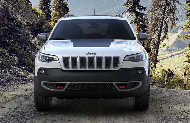 2019 Jeep Cherokee exterior front shot with white paint color showing grille, fascia, and headlights while parked on a forest road
