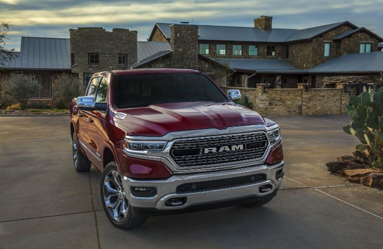2019 Ram 1500 exterior shot with dark red paint color park on a concrete plaza in front of a large stone mansion
