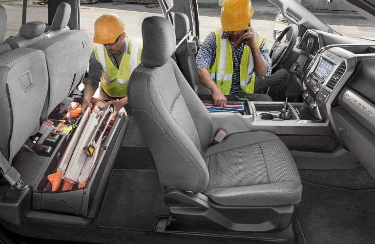 2019 Ford Super Duty with construction workers accessing the lockable, rear under-seat storage