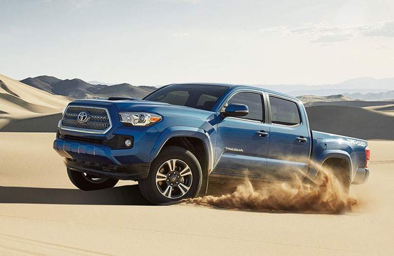 Blue Toyota Tacoma playing in the sand